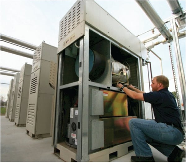 A 65-kW Capstone C65 microturbine equipped with integrated heat recovery is inspected by a technician