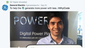 "Twitter post from a GE Digital coder with a poster for the company's new ""Digital Power Plant"" in the background."