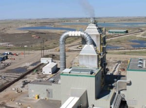 This shot from the roof of SaskPower's Boundary Dam Power Station shows ductwork that carries flue gas from the upgraded Unit 3 to the new carbon capture facility, where sulfur (in the shorter tower) and then carbon dioxide (in the taller tower) are absorbed and stripped before the carbon dioxide is compressed in the building partially visible on the right. From the compression building, the gas is piped underground to a metering station before being sent underground again, either for enhanced oil recovery or permanent geological storage. Source: POWER/Gail Reitenbach