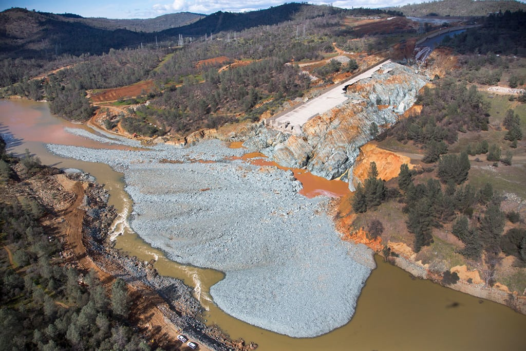 An aerial view of the damaged Oroville Dam spillway site and with a huge debris field in the diversion pool area just below the spillway. The California Department of Water Resources gradually reduced the outflow from the spillway from 50,000 cubic feet per second (cfs) to zero on February 27, 2017. The reduction allows work to begin to remove the debris and reduce water surface elevation in the diversion pool, so the Edward Hyatt Powerplant can go operational. This will allow for better management of reservoir levels during the upcoming spring runoff season. Photo taken February 27, 2017. Dale Kolke / California Department of Water Resources