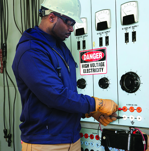 Actual electrician working on an industrial power distribution center.