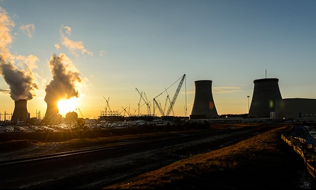 The sun sets behind the Vogtle 1 and 2 cooling towers near the Unit 3 and 4 construction site in Georgia. Courtesy: Georgia Power (March 2016)