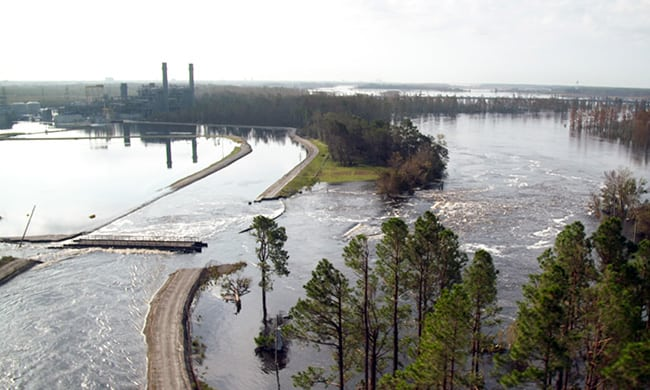 On September 22, the Cape Fear River continued to overtop the northern section of the cooling lake dam at Duke Energy's Sutton plant in North Carolina, a region devastated by floods from Hurricane Florence. Water was still exiting a breach on the southern end of the cooling lake impoundment. The river was expected to surge on Sunday. Courtesy: Duke Energy